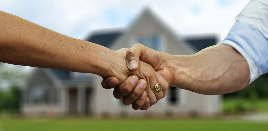 Vendor and buyer shaking hands to handover home