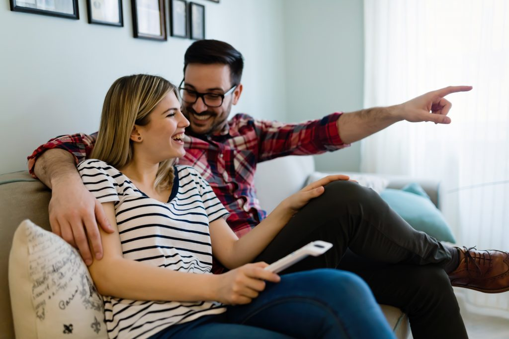 Happy young couple laughing in their home.