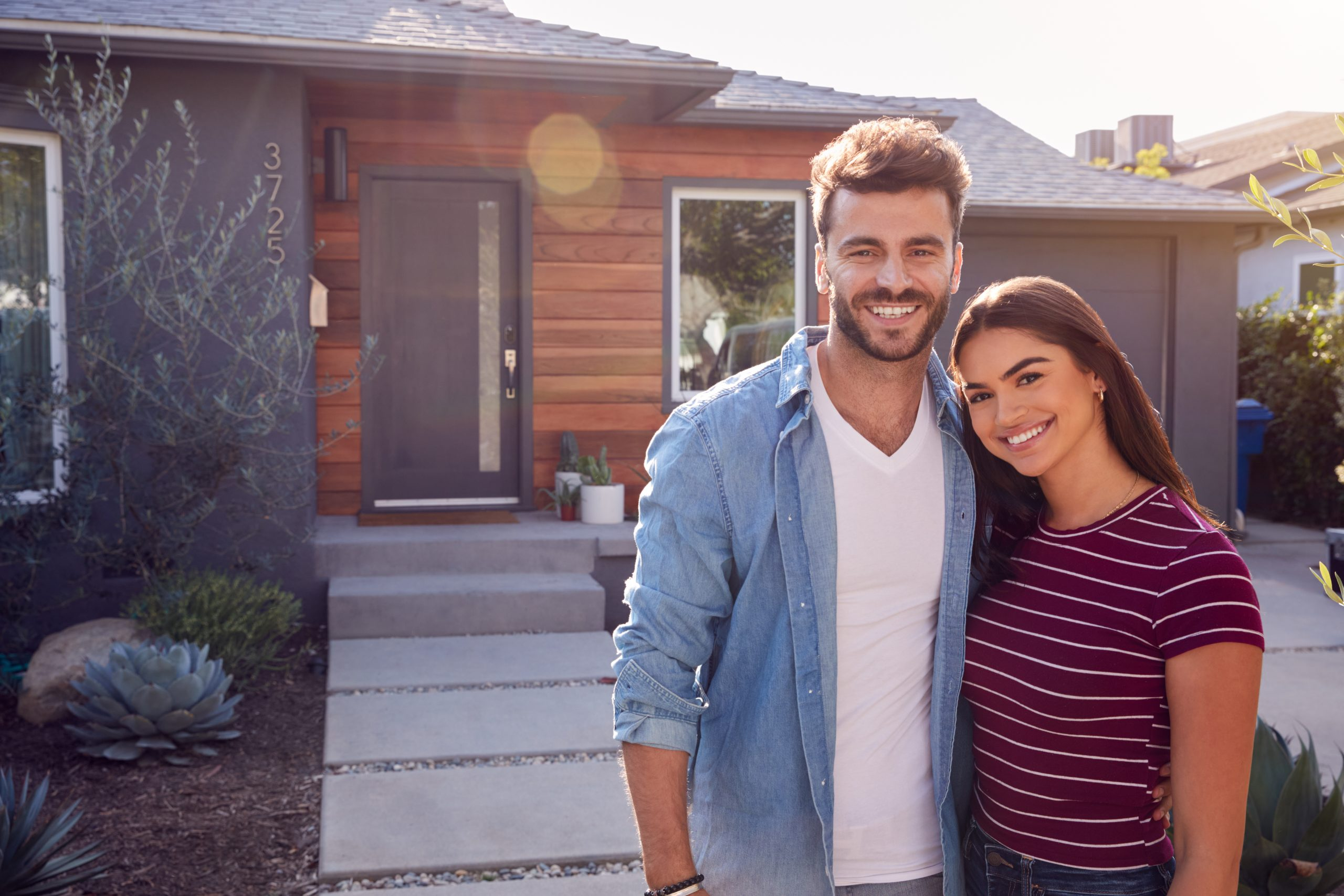 Portrait Of Couple Standing Outdoors In Front Of House