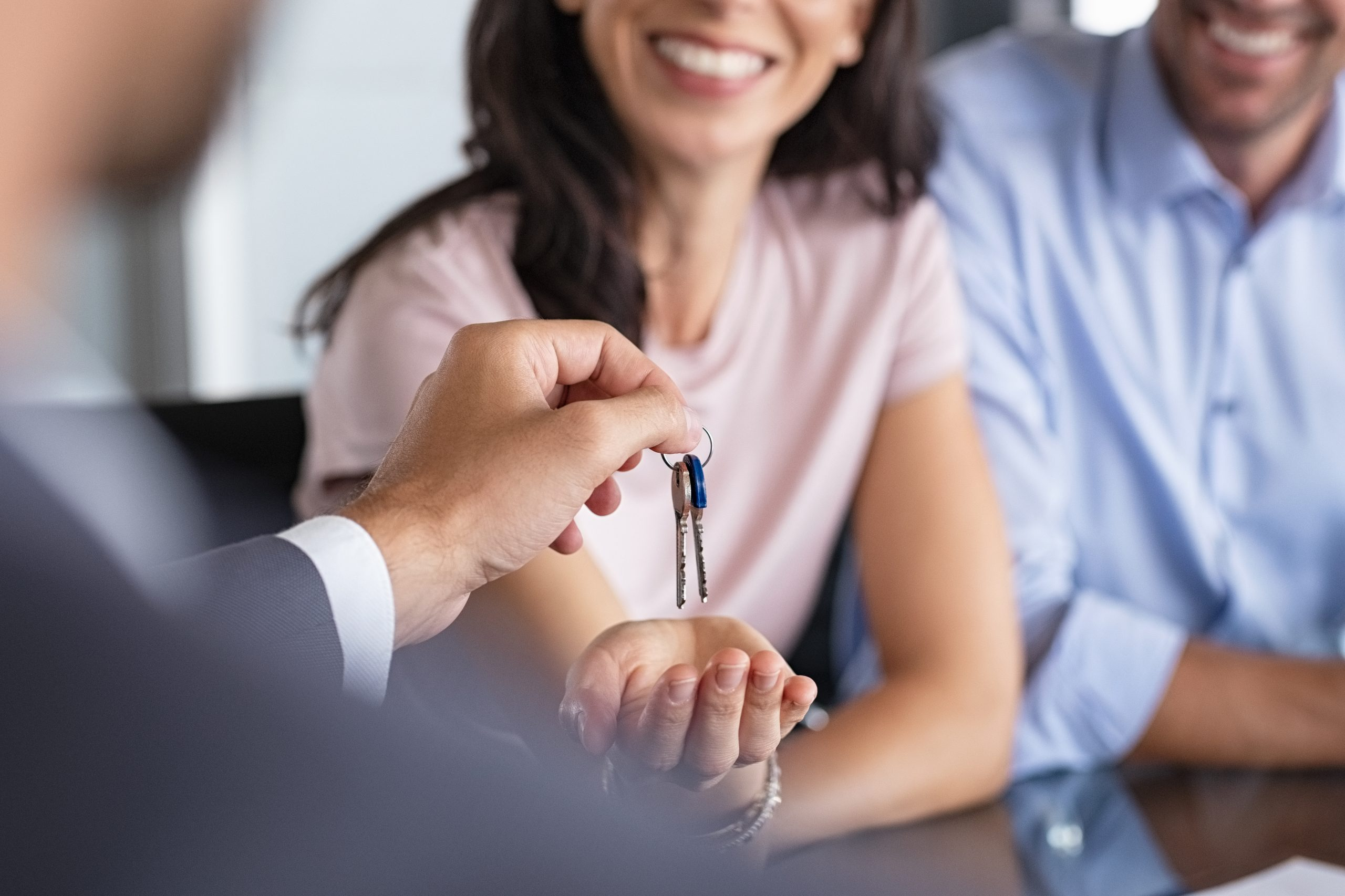 Real estate agent giving keys to apartment owner.