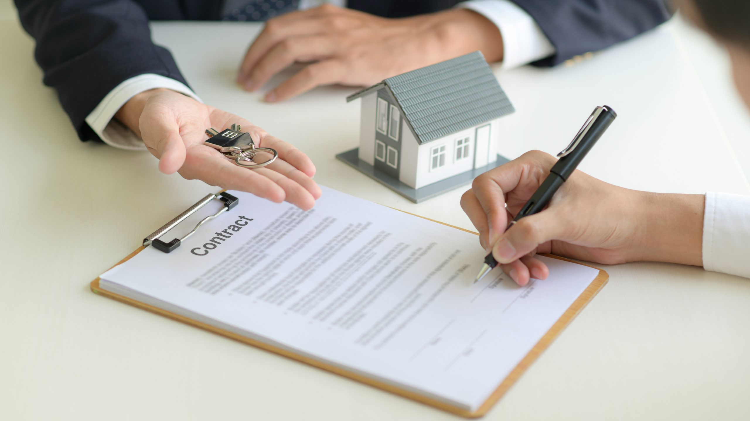 Client signing contract and agent handing over the home keys